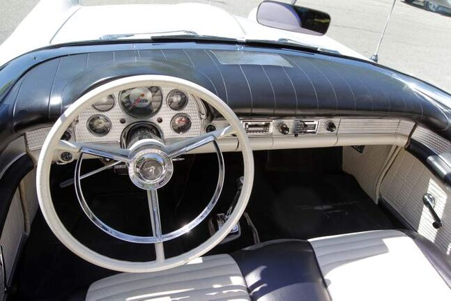 Inside, there's white interior upholstery with black trim, a telescopic steering column, electric clock and a Thunderbird aftermarket AM/FM stereo cassette player.