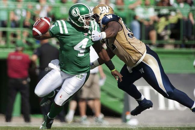 Saskatchewan Roughriders quarterback Darian Durant manages to shake a tackle from Winnipeg Blue Bombers defensive tackle Bryant Turner during the first half of CFL football action in Regina, Sask., Sunday, September 1, 2013. THE CANADIAN PRESS/Liam Richards