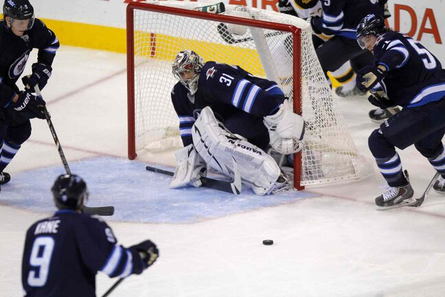 Winnipeg Jets converge on the puck in front of goaltender Ondrej Pavelec.