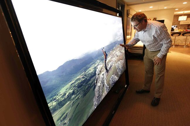 Chris Magas checks the picture resolution on the 85-inch screen of Samsung's $40,000 S9 ultra HD LED television at Advance Electronics Tuesday.