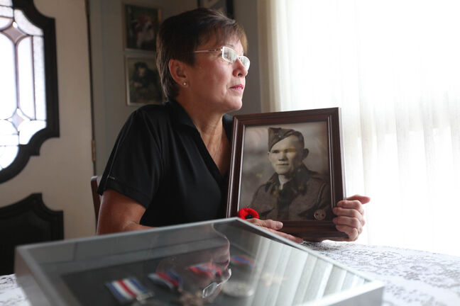 Mae Gulewich holds a photo of her father, John Sinclair, one of the Dufferin Gang wounded in the Second World War.