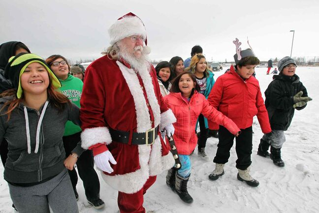 Santa is greeted by kids as he arrives by helicopter at the Black River Anishinabe School on the Little Black River First Nation with MKO Grand Chief David Harper during the Santa Express tour.