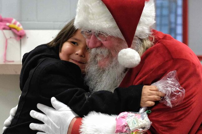 Kayden Swampy, 4, gives Santa a big hug as he visits the Sagkeeng First Nation during his Santa Express tour.