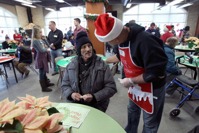 Volunteer Pat Fortin greets patron Mike Szabo during Christmas Eve dinner at the Siloam Mission Tuesday.