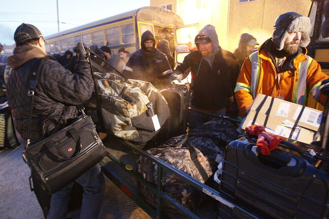 Manitoba Hydro workers load gear onto buses as they arrive back in Winnipeg Tuesday after helping to restore power in Toronto after an ice storm.