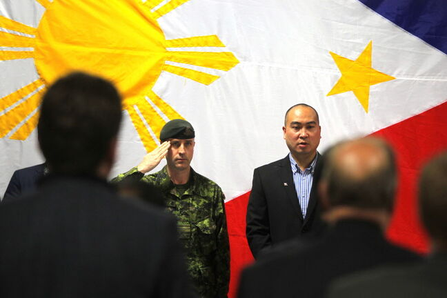 Maj. Robert Meade salutes next to Jon Reyes at Canadian Forces Appreciation Night for DART at the Filipino Senior Citizens Hall on Euclid Avenue Wednesday.