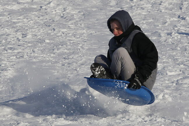 Nathan Devine slides down a snow-covered hill in Kilcona Park Sunday.