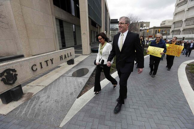 Gord Steeves, accompanied by his wife, Lorrie, goes to city hall in May to sign papers to run for mayor.