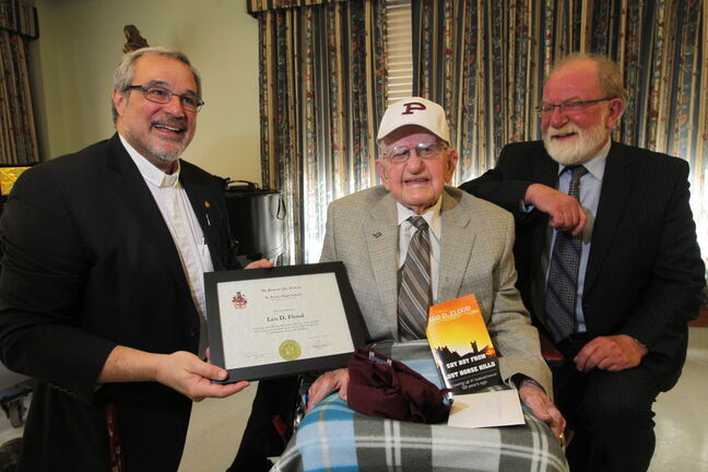 Leo Flood, 100, gets his St. Paul's High School graduation diploma from school president Rev. Leonard Altilia (left) as his proud son, retiring Winnipeg Free Press comment editor Gerald Flood, looks on.