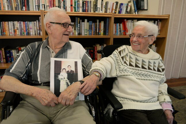 Werner Junghans holds his wedding photo next to Erna, his wife of 66 years. Erna is living at Tuxedo Villa nursing home while Werner, who is ill himself, lives in their home.