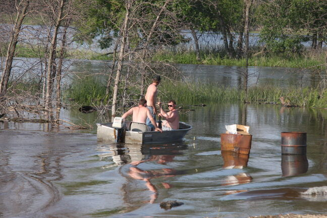 A group of young men travel by boat along the new, swollen shores of Souris River in Melita on Friday evening.