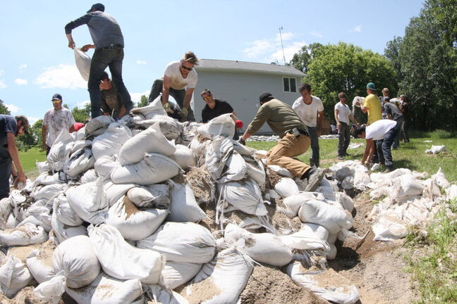Manitoba government employees and other volunteers were busy slinging sandbags at a home west of St. Francois Xavier Wednesday.