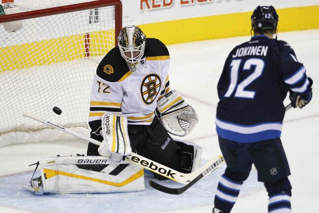 Olli Jokinen watches a shot go past Boston Bruins goaltender Niklas Svedberg during the first period.