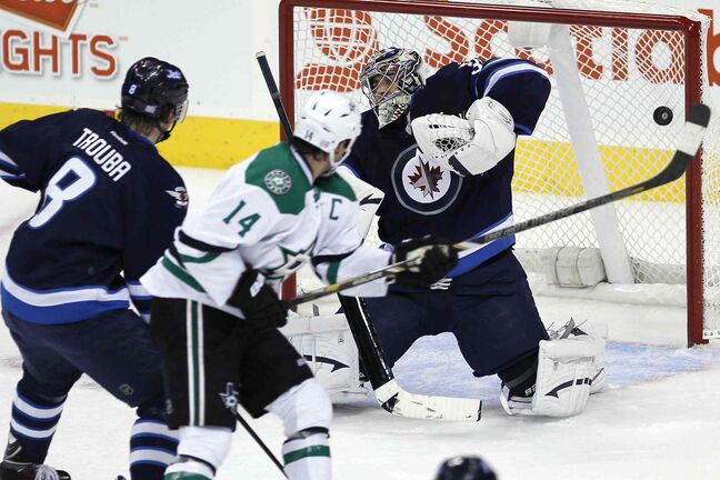 Winnipeg Jets' Jacob Trouba (8) and Dallas Stars' Jamie Benn (14) watch as a shot by Tyler Seguin gets past Jets goaltender Ondrej Pavelec (31) during the first period.