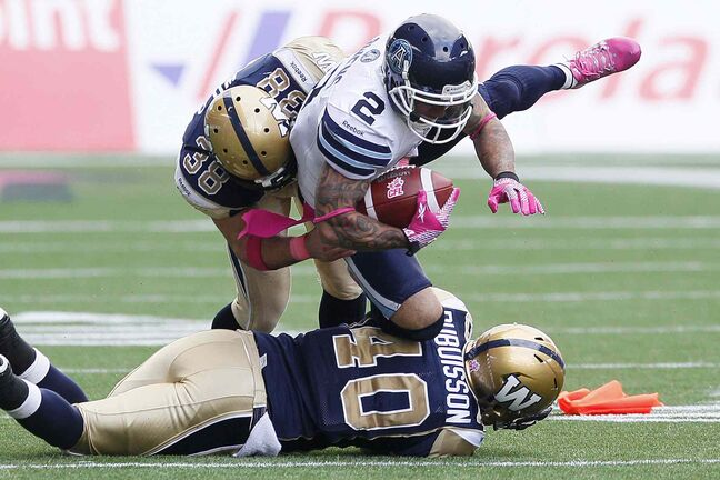 Toronto Argonauts' Chad Owens (2) gets tackled by Winnipeg Blue Bombers' Ian Wild (38) and Philippe Dubuisson-Lebon (40) during the first half.