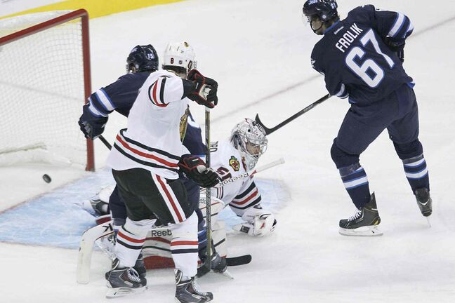 Chicago Blackhawks' goaltender Corey Crawford (bottom) can't stop a shot from the point by Winnipeg Jets defenceman Toby Enstrom as Matt Halishchuk (15) and Michael Frolik (67) of the Jets and Hawks' Nick Leddy (8) look for the rebound during the first period.