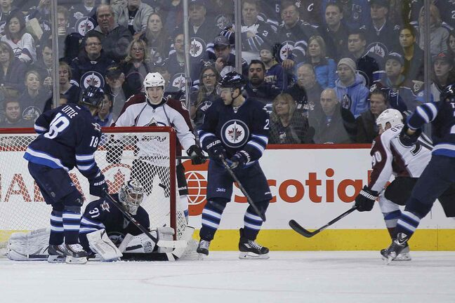 Colorado Avalanche's Ryan O'Reilly (90) scores on Winnipeg Jets goaltender Ondrej Pavelec (bottom) during the second period.