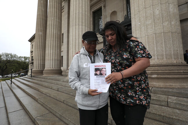 RUTH BONNEVILLE / WINNIPEG FREE PRESS Carolyn Carpenter and April's mom, Cheryl Carpenter,  hold a missing person poster of April on Thursday on the steps of the legislature. Family members of of April Carpenter confirmed that the body pulled from the Red River Wednesday afternoon was April.