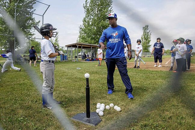 Former Blue Jays second baseman Homer Bush gives nine-year-old Marcus Burak pointers on batting.