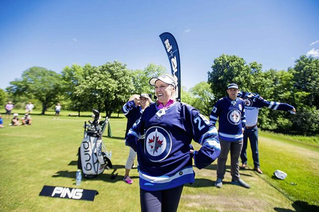 Five-time LPGA tournament winner Brooke Henderson tries on a signed Jets jersey she received as a gift after doing a clinic with the Future Pros Program at the St. Charles Country Club in Winnipeg.