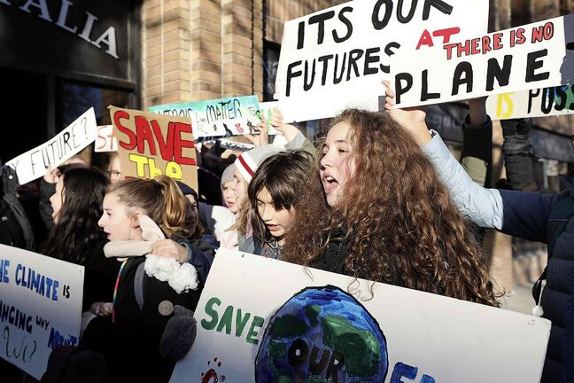 RUTH BONNEVILLE / WINNIPEG FREE PRESS      Ecole River Heights School grade seven students hold signs  outside Winnipeg South Centre, (Liberal) MP Jim Carr's constituency office lobbying the government for laws to protect the planet on Friday.      See story.     Dec 7th, 2018