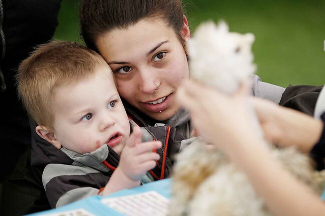 Alexa Twerdochlib with her son Nikko watch as his pet ostrich DeDe is treated at the Teddy Bear Picnic.</p>