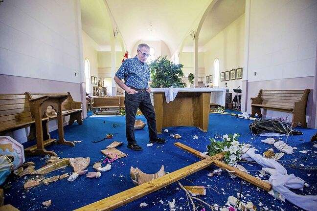 Eugene Bernardin examines the rubble of smashed sculptures on the vandalized altar at St. Francois Xavier Catholic Church.