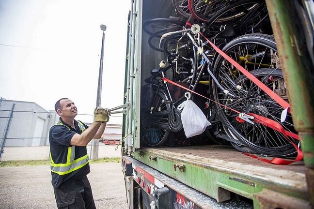 MIKAELA MACKENZIE / WINNIPEG FREE PRESS  Grant Houlden, truck driver for J & T Trucking, opens the shipping container filled with old Dutch bikes in Winnipeg on Tuesday, June 11, 2019. For Alex Paul story.    Winnipeg Free Press 2019.