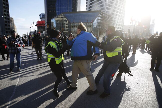 JOHN WOODS / WINNIPEG FREE PRESS A person speaking out against protesters in support of Wet'suwet'en blockades who closed Portage and Main to traffic in Winnipeg Wednesday, February 26, 2020 is removed by police after getting surrounded by protesters.   Reporter: ?