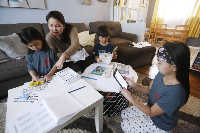 Jennifer Valencia home schools her children Jiahna, 6, Jian, 7, and Jyzella, 9, in their Elmwood home. School divisions are grappling with how to handle the digital divide as they promote online learning during satellite school. Some are sending home laptops, others are sticking to paper packages. The Valencia family is focused on paper work. Valencia says they only have one slow desktop, so she's been printing out all their assignments. (John Woods / Winnipeg Free Press)