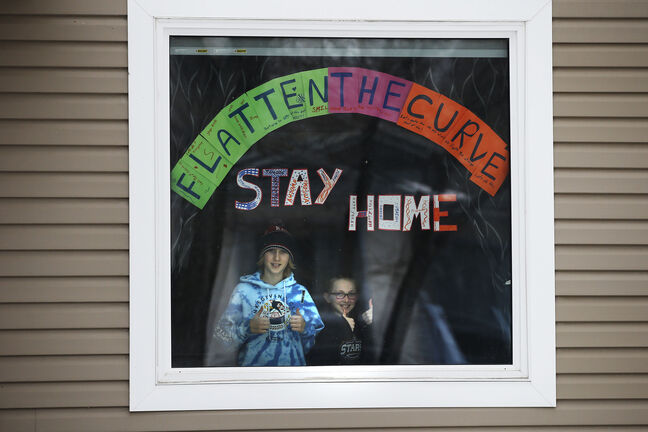 "JOHN WOODS / WINNIPEG FREE PRESS Everett Winters, 12, and sister Victoria, 9, made a sign in their Norwood home window reminding Winnipeggers what they have to do to ""Flatten The Curve"" during this time of COVID-19 isolation in Winnipeg Tuesday, March 24, 2020.   Reporter: Standup"