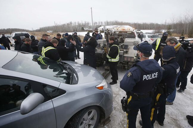JOHN WOODS / WINNIPEG FREE PRESS People pray as a tow truck is moved in to remove a van as RCMP officers and Manitoba Justice officials blocked the entrance to Church of God Restoration in Sarto, just south of Steinbach, to enforce Manitoba Health COVID-19 orders Sunday, November 29, 2020.   Reporter: Abas