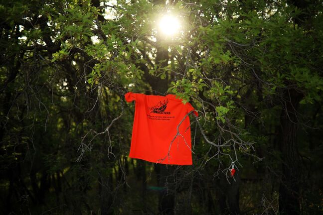 Brandon Sun 02062021 An orange shirt that reads Every Child Matters hangs in the trees at the site of the former Brandon Indian Residential School near other items left in memorial of the children who died while attending the school. Research has estimated that over 100 children are buried at various sites connected to the former school grounds. Last week research done by the Tk'emlúps te Secwe´pemc First Nation in BC uncovered a mass unmarked grave of 215 children who died while at the Kamloops Indian Residential School, a horrific finding and triggering event for all Canadian First Nations people, which also triggered a national reflection on the abuses of all Canadian residential schools. (Tim Smith)