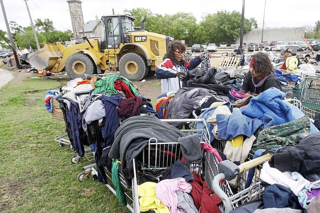 JOHN WOODS / WINNIPEG FREE PRESS Desirae, right, and another resident look through carts of clothing as city crews dismantle camps on Austin Street and Henry Avenue in downtown Winnipeg in June.