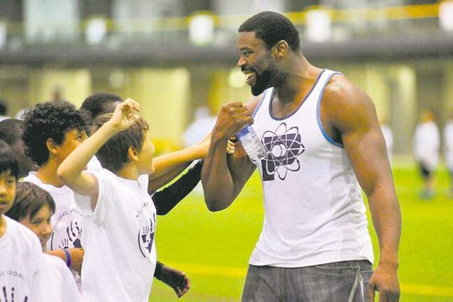 Israel Idonije interacts with young players at a football camp at the University of Manitoba earlier this month.