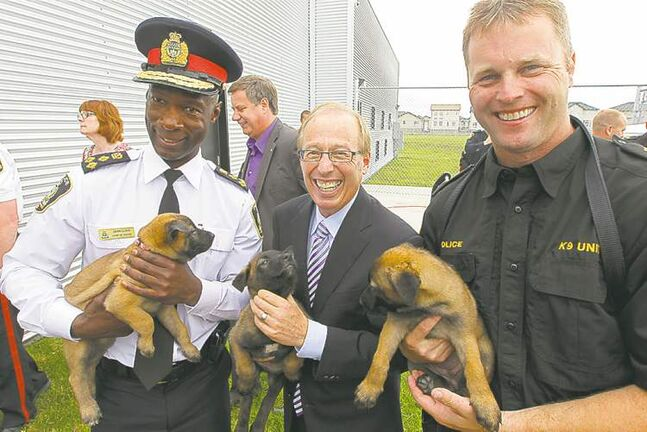 From left, Chief Devon Clunis, Mayor Sam Katz and Sgt. Dave Bessason show off some of the newest residents of the new Winnipeg Police Service Canine Unit building Winnipeg Police Service canine unit building on Dugald Road.