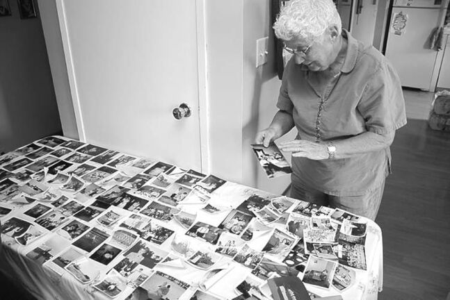 Dorothy Jago looks over photos spanning eight decades recovered from her flooded Reston basement.