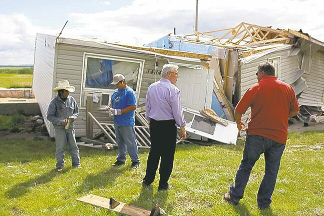 Premier Greg Selinger tours the damage Monday from the tornado at Sioux Valley.