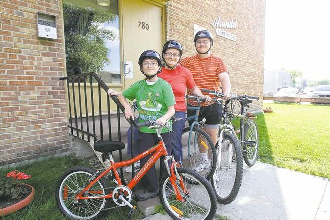 Shelley Sauvé and her two sons Miguel, 10, and Gary, 17, ride their bikes during the summer months to save money.