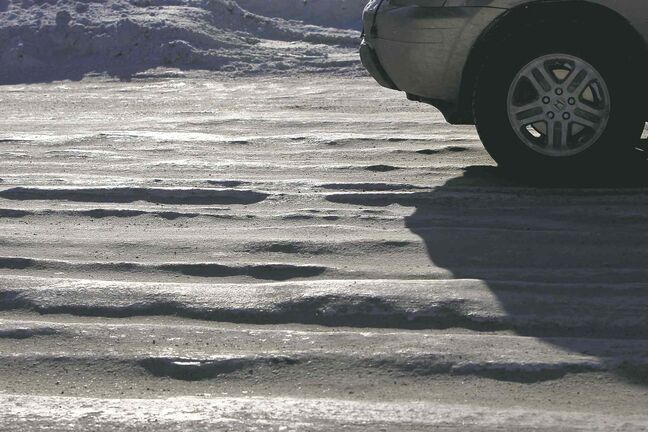 Icy, rutted patches on Logan Avenue near Highway 90 Monday. The looming grader plow will clear a lot of potentially dangerous ruts that have developed throughout the city.