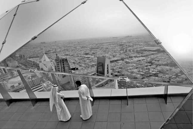 Saudi men on the mirrored viewing level of Al-Faisaliyah Center in Riyadh, Saudi Arabia.