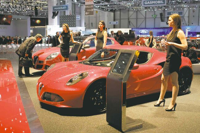 Models pose in front of the new Alpha Romeo C4 at the Geneva auto show.