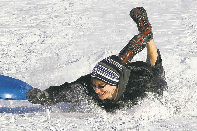 William Friesen takes a tumble while sledding at Kilcona Park Sunday.