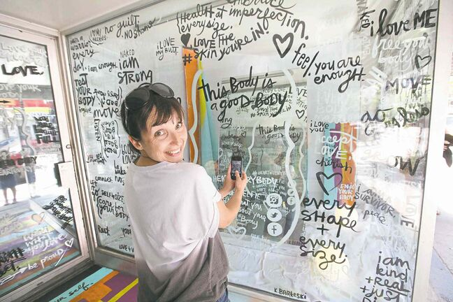 Artist Kal Barteski takes a selfie in the glassed-in space she created to promote positive body-image messages. The space is at the Women's Health Clinic on Graham Avenue.