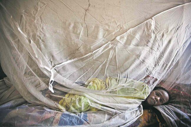 A woman sick with malaria rests on a bed in North Darfur.