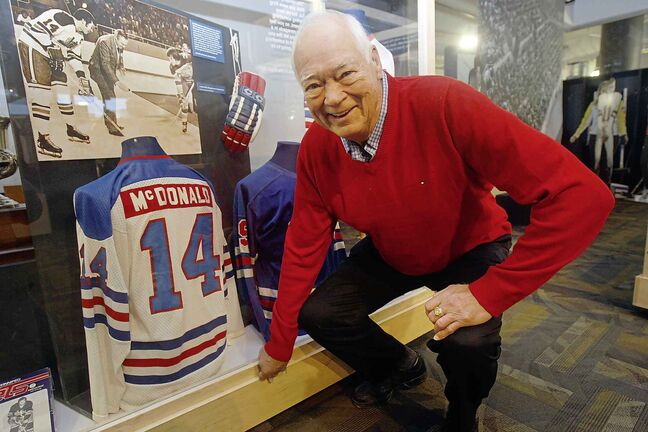 Hockey legend Ab McDonald  at the Manitoba Sports Hall of Fame in front of the exhibit that includes his jersey.