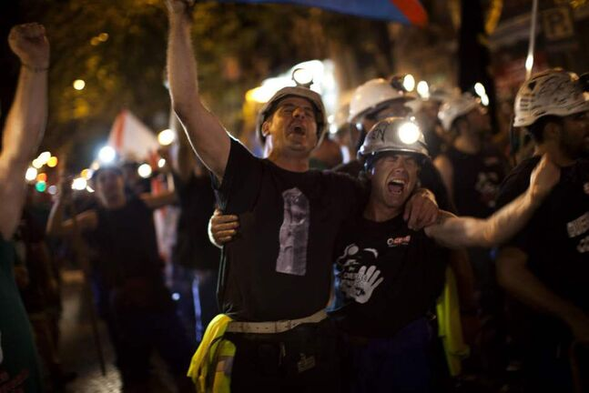Miners sing as they march along a street after walking for more than 20 days from the northern Asturias and Leon regions, as many as 400 kilometers (250 miles), on their way to Puerta del Sol, the Spanish capital's most emblematic square in Madrid. (AP Photo/Emilio Morenatti)