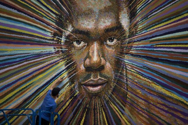 Australian street artist James Cochran spray paints a portrait of Usain Bolt, Jamaica's world record holder in the 100 and 200 metre sprints, on the wall of a building beside a car park in east London. Cochran, who has been a street painter for 20 years, has been working on the piece for four days and is due to finish it later today. (AP Photo/Matt Dunham)