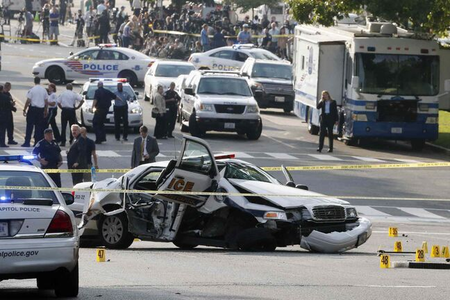A wrecked U.S. Capitol police car blocks Constitution Avenue NW.