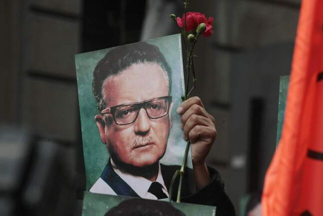 A man holds a photograph of Chile's late President Salvador Allende outside La Moneda presidential palace in Santiago, Chile, Wednesday. Chile is marking the 40th anniversary of the military coup by Gen. Augusto Pinochet that overthrew Allende on Sept. 11, 1973.